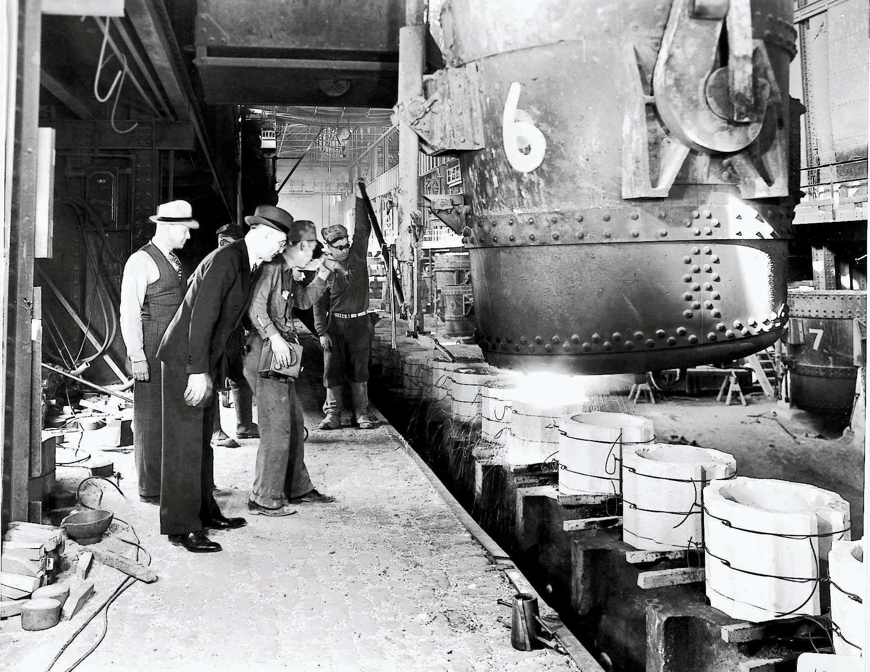 H.H. Timken (foreground) watches steel pouring at the company's first melt shop in 1917.